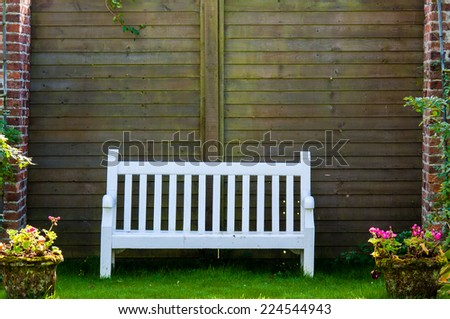 White Wooden garden bench in English garden, retro color filter applied
