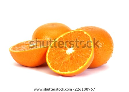 Whole and half slices of fresh oranges over white background