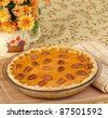 Whole pumpkin pie with pecans on a tray - stock photo