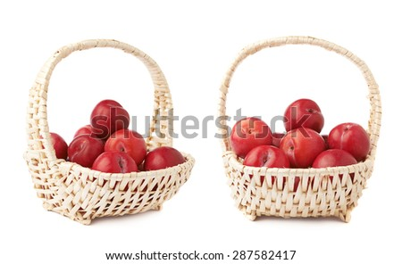 Wicker basked filled with multiple red victoria plums isolated over the white background, set of two different foreshortenings