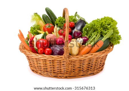 Wicker basket full with various fresh vegetables on white