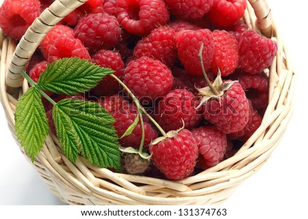 Wicker basket of fresh raspberries isolated on white background, top view