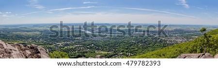 Wide panorama aerial view from Mount Saint-Hilaire in Quebec, Canada. Montreal suburbs and small towns down the hill. Montreal city at horizon.