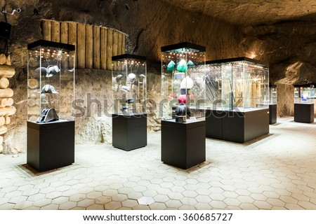 Wieliczka - Poland - April 23, 2015: One of the chambers of Salt Mine Museum Exhibition. In glass-case are shown hats, caps, helmets and other miners accesories.