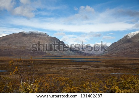 Wilderness of Alaska tundra in late fall with snow on mountains