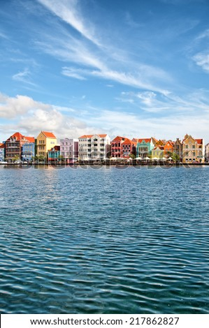WILLEMSTAD (CURACAO) - CIRCA DECEMBER 2013 - View across the sea of the Willemstad, Curacao, Dutch Antilles waterfront with historic colorful Caribbean architecture and seafront esplanade
