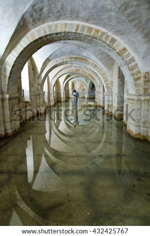 "Winchester, Hampshire, UK - February 07, 2016: The flooded Crypt of Winchester Cathedral containing the sculpture ""Sound II"" by british artist Antony Gormley. Winchester, UK on February 07, 2016."