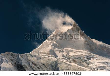 Wind blowing snow from mountain peak. Nepal, Manaslu
