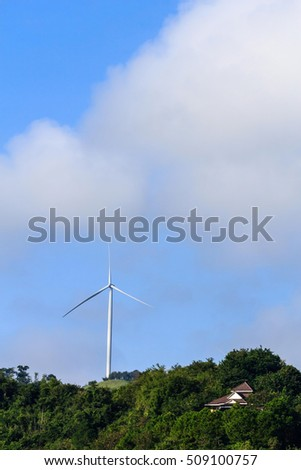 Wind turbine renewable energy source summer landscape with blue sky on the mountains.