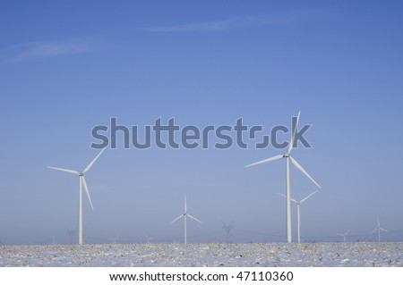 Wind turbines and distant power pylons stand above wintry corn field in northern Illinois