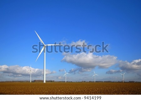 Wind Turbines in the field with blue cloudy sky