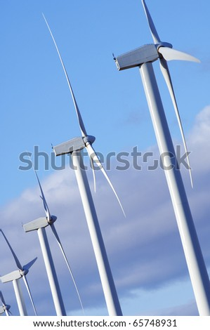 windmills group with blue and cloudy sky