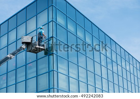 Window cleaner working on a glass facade in a crane