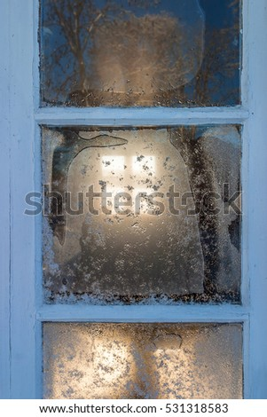 Window with frost and sunlight