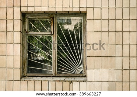 Window with steel bars on tile wall on sunny day