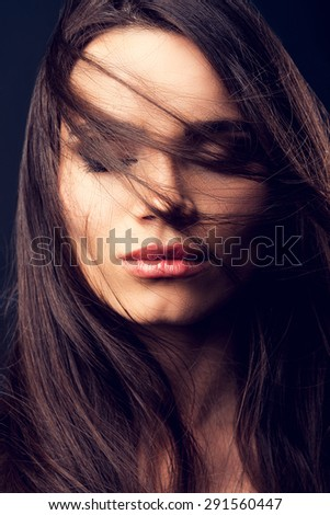 Windswept beauty. Beautiful young woman keeping eyes closed and covering her face by hair while standing against black background