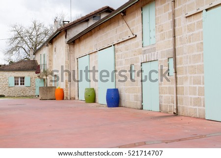 Wine barrels in the background of an ancient house. France.