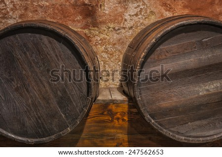 Wine cask barrels stacked in the old cellar of the winery