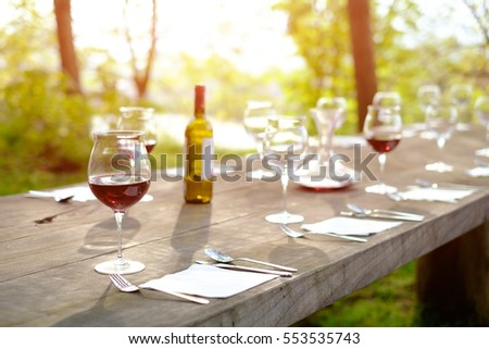 Wine glasses on a wooden table in the countryside shallow depth of field