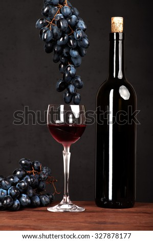 Wine in the bottles and wine in the glass on a dark background; grapes; corkscrew; corks; the substrate for the wine list; drinking wine; wine tasting; wine list