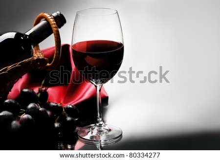 Wineglass and bottle of red wine in basket on black and white background.