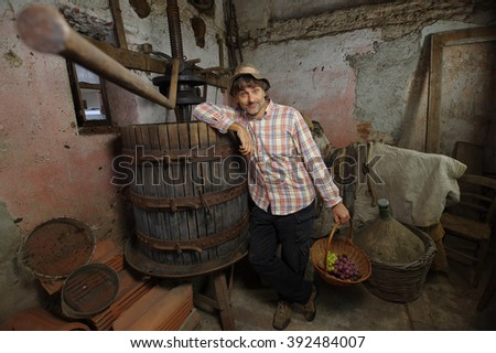 winemaker with grapes at old wine press machine in a cellar