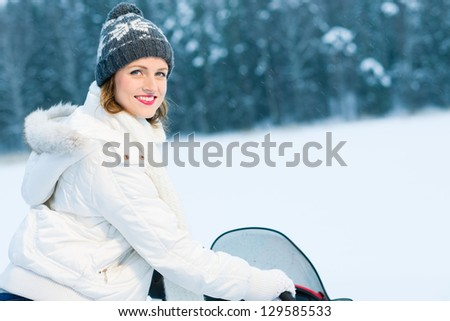 Winter, beautiful woman and a snowmobile, horizon format