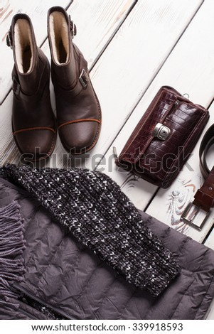 Winter collection of men's clothing and accessories on a wooden background.