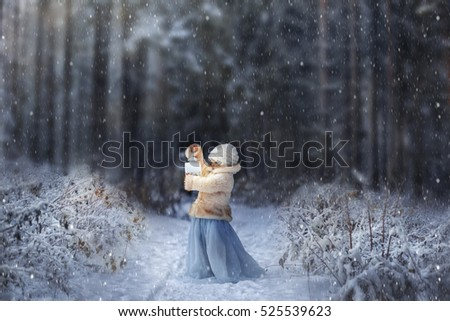 Winter fairytale. Little girl with lightning in frozen forest on Christmas eve