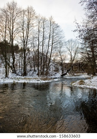 winter forest covered with snow and unfrozen river, morning