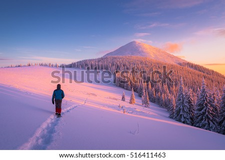 Winter hiking in the mountains. The guy goes down the path in the snow. Beautiful sunset. Landscape with a mountain top and spruce forest
