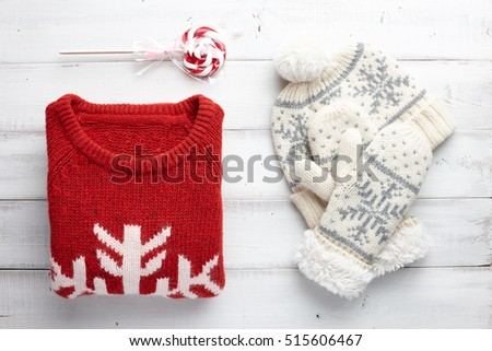 Winter holiday knitted sweater, mittens and cap on white wooden background. Christmas fashion clothing style.