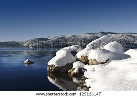 Winter lake. Snowcapped rocks foreground, blue sky