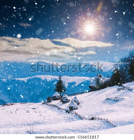 Winter landscape with cottages and hay bales in rural landscape. Christmas concept
