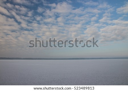 Winter landscape with lake and blue sky