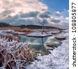 Winter landscape with snowy river and dry tree, majestic sky - stock photo