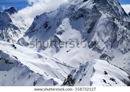Winter mountains with snow cornice in nice sun day. Caucasus Mountains, region Dombay. Mountainside of Dombai-Ulgen. View from the top of Musa Achitara.