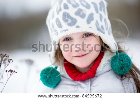 Winter portrait of adorable happy child girl in warm clothes