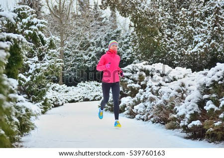 Winter running and fitness in park: happy woman runner jogging in snow, outdoor sport concept
