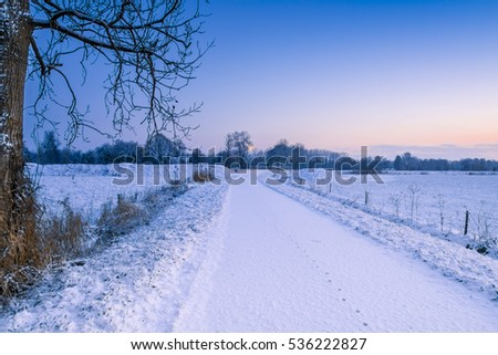 Winter scenery with a snowy bridge over a canal