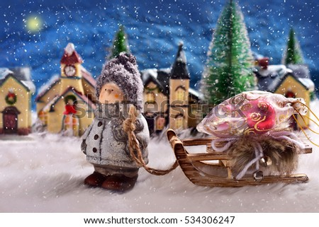 winter snowy night scene in small town with a boy pulling a sled with a bag of christmas presents
