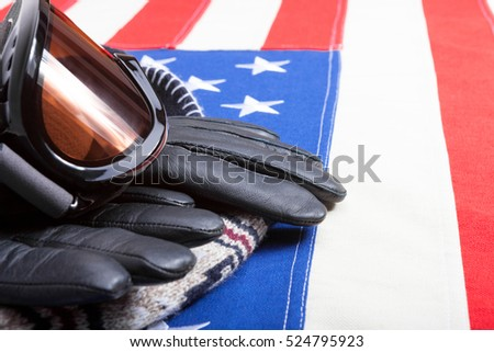 Winter sport goggles with gloves and a hat over USA flag