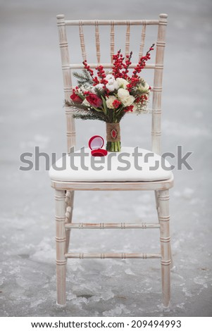 Winter wedding bouquet with pine cones and red and white flowers on a chair with a ring