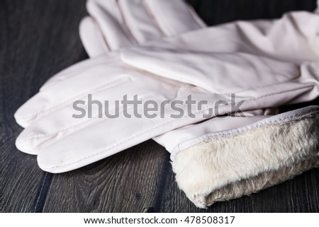 Winter white leather gloves with fur on black wooden table