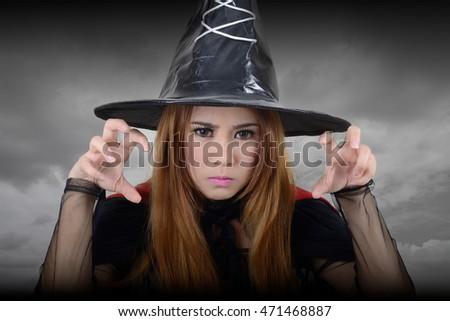 Witch looking toward and try to casts a spell in dark background.