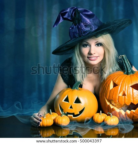 Witch with Halloween Pumpkins. Happy Beautiful Blonde Girl
