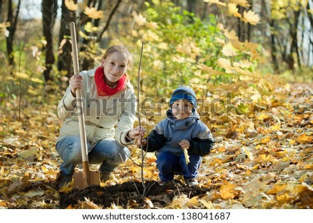 woman and boy with spade outdoors planting  tree in autumn