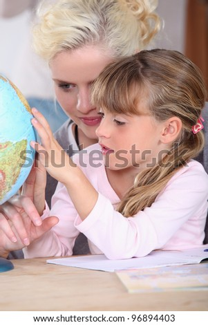 Woman and child looking at a globe