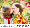 Woman and child with bouquet of flowers against green background. Spring family holiday concept. Mother`s day - stock photo