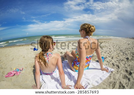 Woman and daughter relaxing on a beautiful beach together on vacation